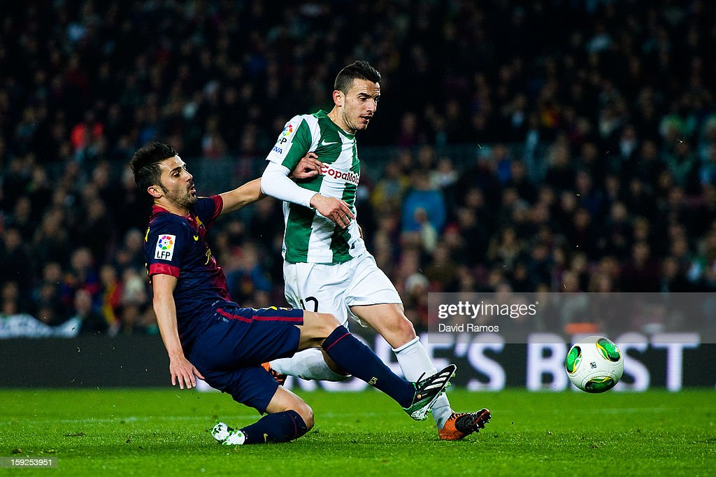 <a gi-track='captionPersonalityLinkClicked' href=/galleries/search?phrase=David+Villa&family=editorial&specificpeople=467566 ng-click='$event.stopPropagation()'>David Villa</a> of FC Barcelona shoots towards goal under a challenge by Vicenzo Rennella of Cordoba CF during the Copa del Rey round of sixteen second leg match between FC Barcelona and Cordoba CF at Camp Nou on January 10, 2013 in Barcelona, Spain.