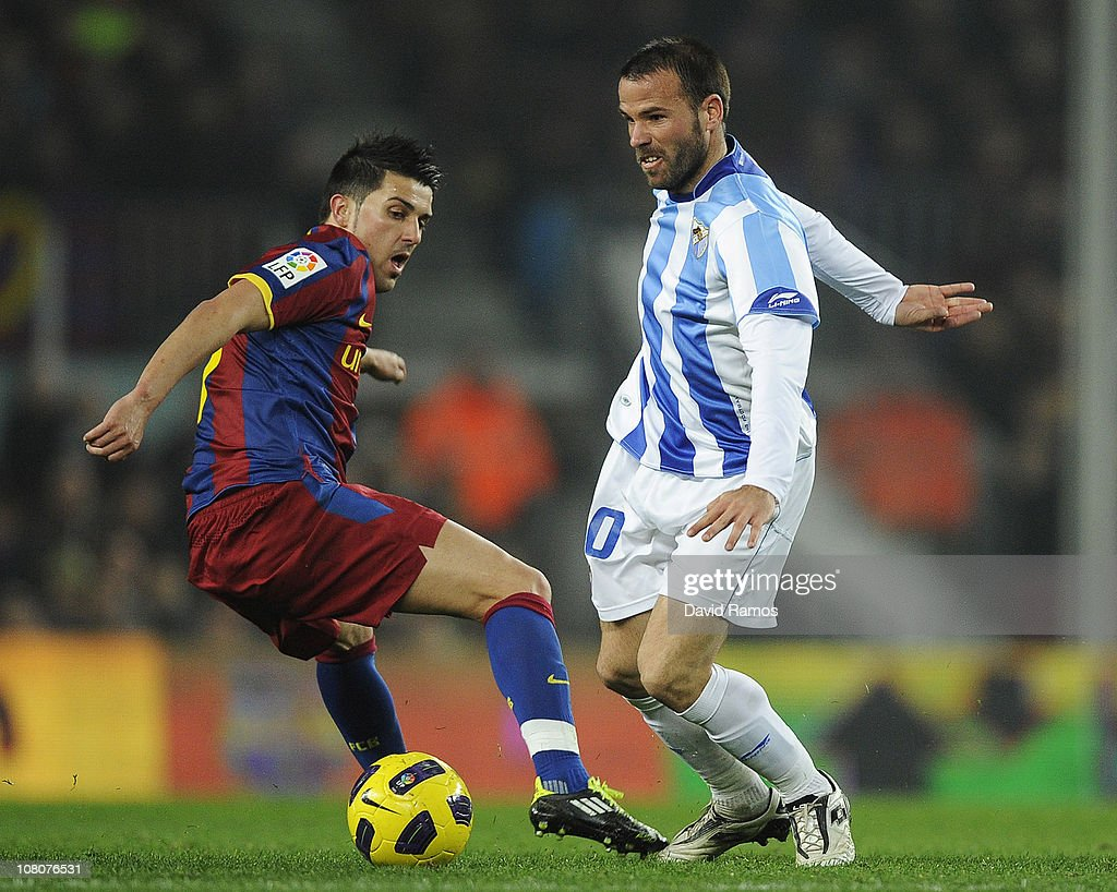 <a gi-track='captionPersonalityLinkClicked' href=/galleries/search?phrase=David+Villa&family=editorial&specificpeople=467566 ng-click='$event.stopPropagation()'>David Villa</a> of FC Barcelona (L) vies for the ball Apono of Malaga (L) during the La Liga match between FC Barcelona and Malaga at Nou Camp on January 16, 2011 in Barcelona, Spain. Barcelona won 4-1.