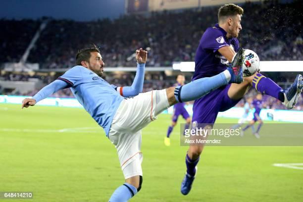 David Villa of New York City FC kicks the ball toward the goal in front of Jose Aja of Orlando City SC during a MLS soccer match between New York...