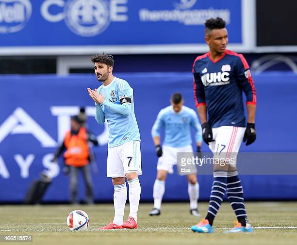 David Villa of New York City FC prepares for the start of the inaugural game of the New York City FC as Juan Agudelo of New England Revolution looks...