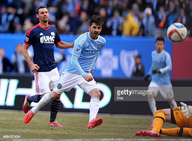 David Villa of New York City FC scores a goal in the first half as Andy Dorman of New England Revolution defends during the inaugural game of the New...