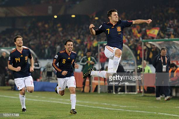 David Villa of Spain celebrates scoring the opening goal with team mates Xabi Alonso and Xavi Hernandez during the 2010 FIFA World Cup South Africa...