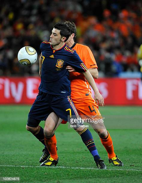 David Villa of Spain controls the ball with Joris Mathijsen of the Netherlands during the 2010 FIFA World Cup Final between the Netherlands and Spain...