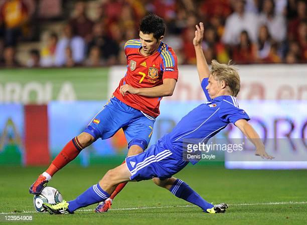 David Villa of Spain is tackled by Martin Rechsteiner of Liechtenstein during the EURO 2012 Qualifier match between Spain and Liechtenstein at...