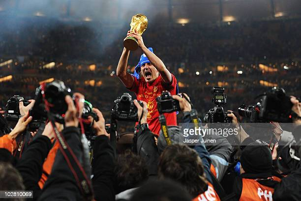 David Villa of Spain lifts the World Cup trophy as photographers clamour following the 2010 FIFA World Cup South Africa Final match between...
