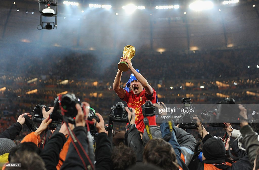 <a gi-track='captionPersonalityLinkClicked' href=/galleries/search?phrase=David+Villa&family=editorial&specificpeople=467566 ng-click='$event.stopPropagation()'>David Villa</a> of Spain lifts the World Cup trophy as photographers clamour following the 2010 FIFA World Cup South Africa Final match between Netherlands and Spain at Soccer City Stadium on July 11, 2010 in Johannesburg, South Africa.