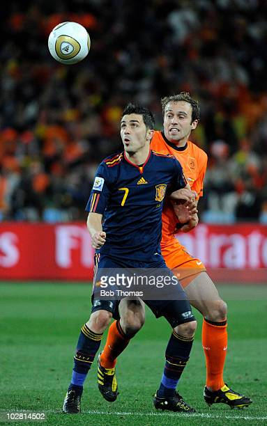 David Villa of Spain watches the ball with Joris Mathijsen of the Netherlands during the 2010 FIFA World Cup Final between the Netherlands and Spain...