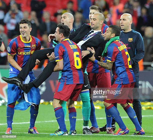David Villa Xavi Hernandez Danny Alves and Victor Valdes of Barcelona lift Coach Pep Guardiola in celebration after the 2011 UEFA Champions League...