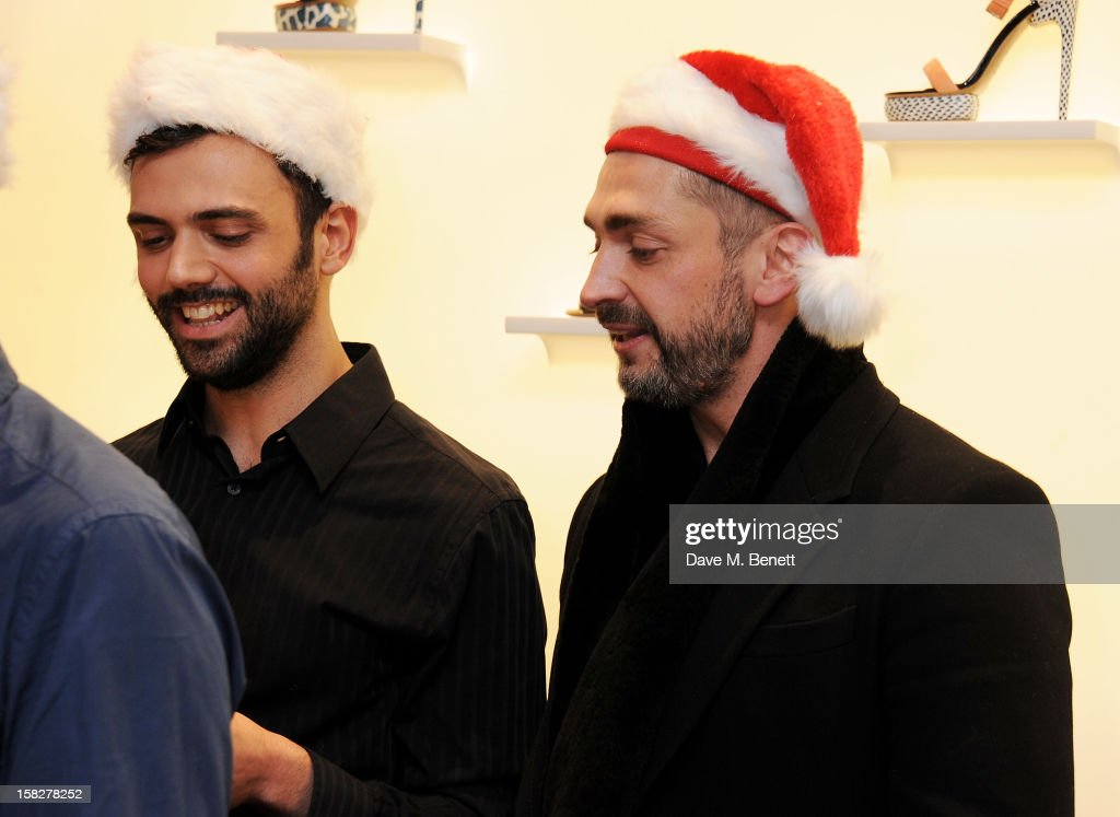 David Waddington (R) performs with The Bistotheque Choir at a Christmas drinks hosted by designer Nicholas Kirkwood to celebrate his partnership with Chambord black raspberry liquer, and launch the limited edition shoe 'The Chambord' at the Nicholas Kirkwood Mount Street store on December 12, 2012 in London, England.