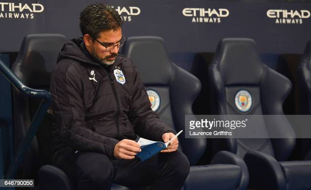 David Wagner manager of Huddersfield Town sits on the team bench as he reads the match day programme prior to The Emirates FA Cup Fifth Round Replay...