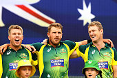 David Warner Aaron Finch and George Bailey of Australia sing the Australian national anthem before the start of play during the final match of the...