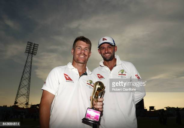 David Warner and Nathan Lyon of Australia pose with the Man of the Series trophy after Australia defeated Bangladesh on day four of the Second Test...