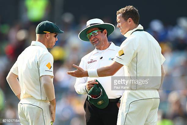 David Warner and Peter Siddle of Australia share a moment with umpire Aleem Dar during day two of the First Test match between Australia and South...