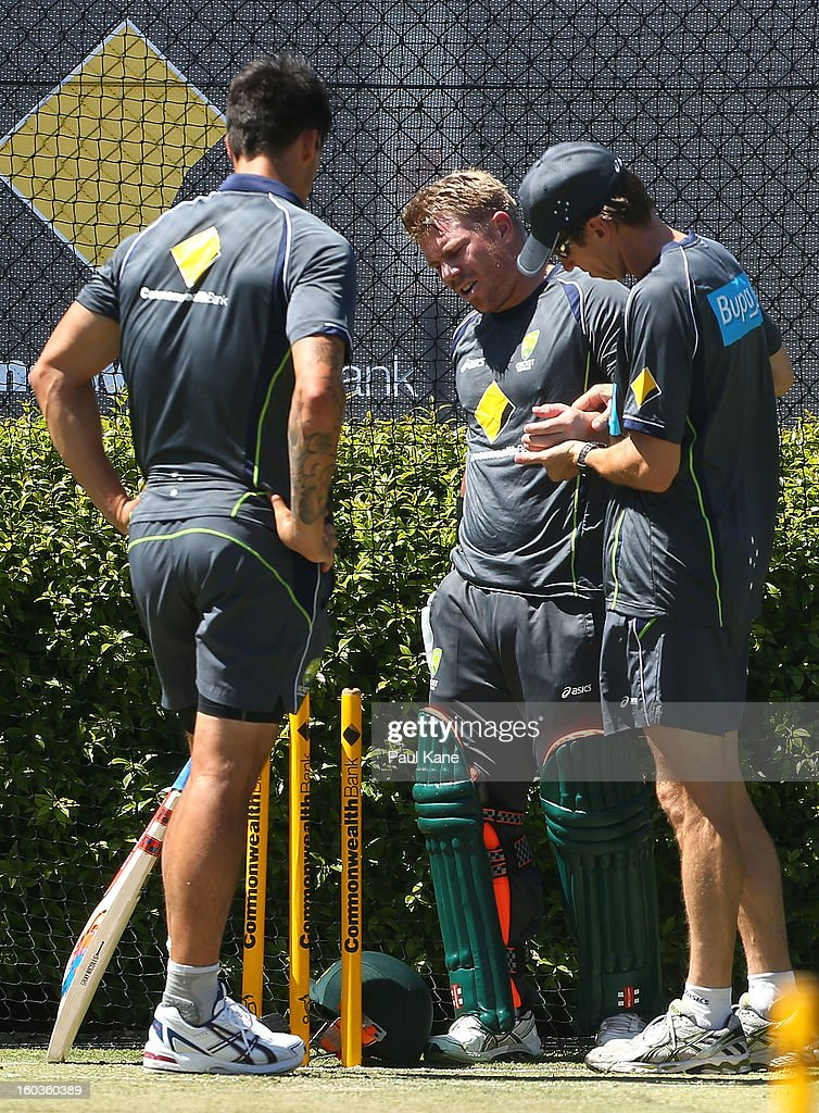 David Warner is checked by rehabilition manager Kevin Sims after being struck on the left hand by Mitchell Johnson during an Australian One Day International training session at WACA on January 30, 2013 in Perth, Australia.