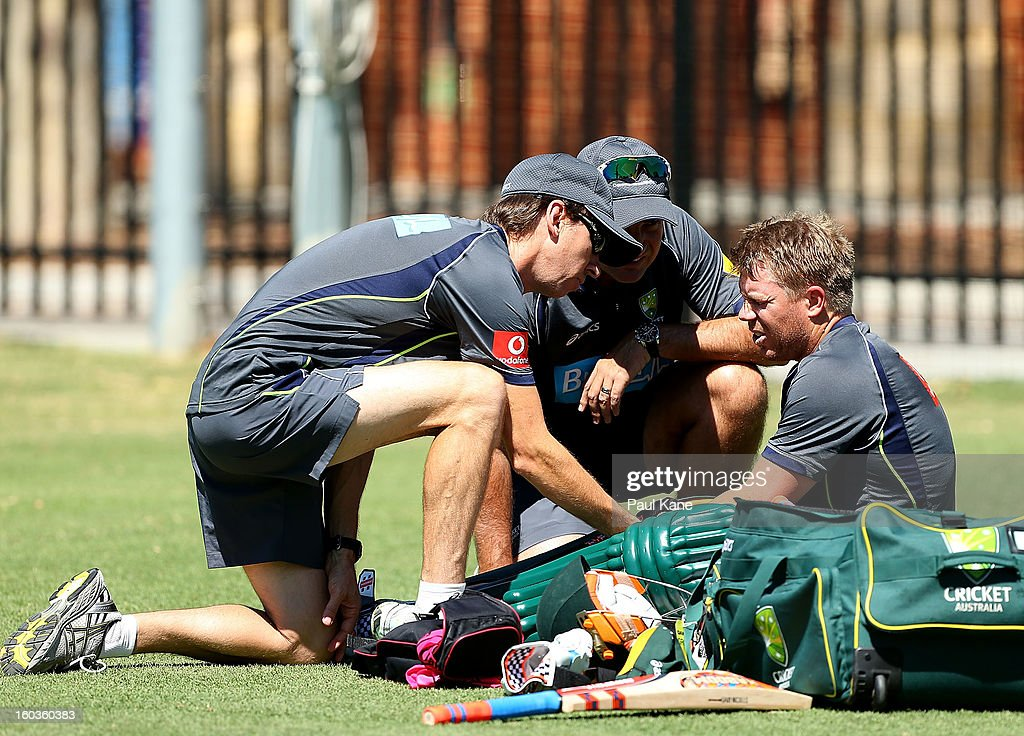 David Warner is checked by rehabilition manager Kevin Sims and coach Mickey Arthur after being struck on the left hand by Mitchell Johnson during an Australian One Day International training session at WACA on January 30, 2013 in Perth, Australia.