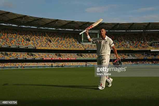David Warner of Australia acknowledges the crowd as he leaves the field after scoring 163 during day one of the First Test match between Australia...
