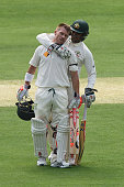 David Warner of Australia celebrates reaching his century with Usman Khawaja during day one of the First Test match between Australia and New Zealand...
