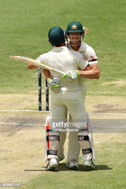 David Warner of Australia embraces Cameron Bancroft of Australia after winning the test during day five of the First Test Match of the 2017/18 Ashes...