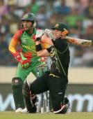 David Warner of Australia hits a boundary as Mushfiqur Rahim of Bangladesh looks on during the ICC World Twenty20 Bangladesh 2014 match between...