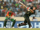 David Warner of Australia hits a six as Mushfiqur Rahim of Bangladesh looks on during the ICC World Twenty20 Bangladesh 2014 match between Bangladesh...