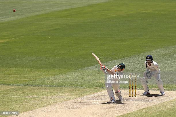 David Warner of Australia hits the ball for six in front of Indian keeper Wriddhiman Saha during day four of the First Test match between Australia...