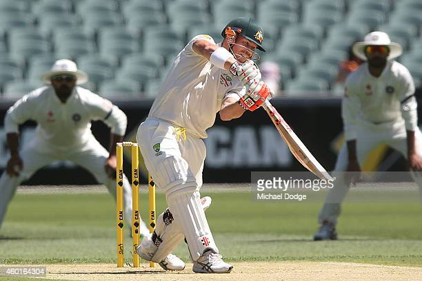 David Warner of Australia hits the ball to the boundary off Mohammed Shami of India during day one of the First Test match between Australia and...