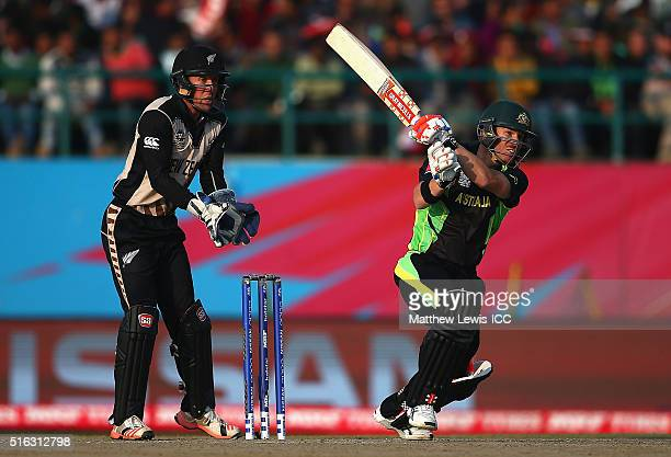 David Warner of Australia hits the ball towards the boundary as Luke Ronchi of New Zealand looks on during the ICC World Twenty20 India 2016 match...