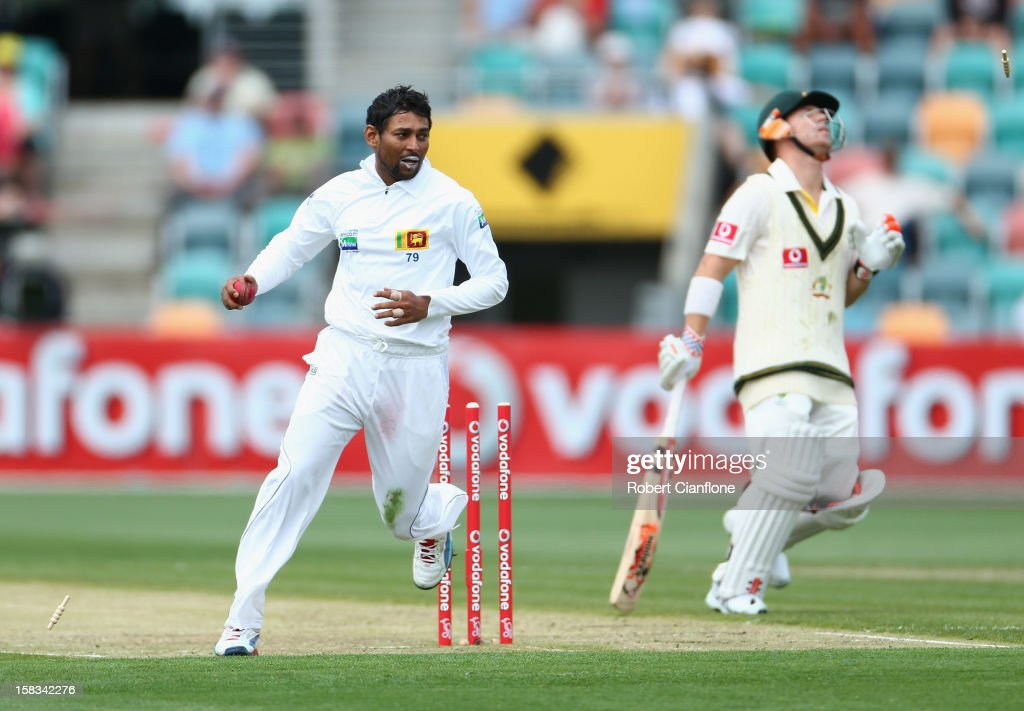 David Warner of Australia is run out by <a gi-track='captionPersonalityLinkClicked' href=/galleries/search?phrase=Tillakaratne+Dilshan&family=editorial&specificpeople=239186 ng-click='$event.stopPropagation()'>Tillakaratne Dilshan</a> of Sri Lanka during day one of the First Test match between Australia and Sri Lanka at Blundstone Arena on December 14, 2012 in Hobart, Australia.