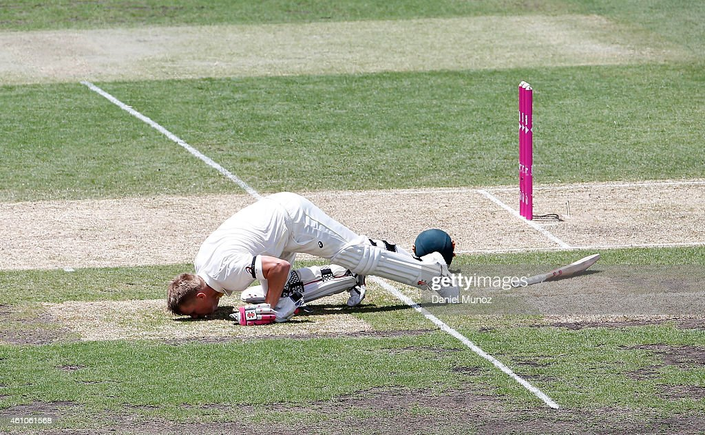 David Warner of Australia kisses the ground after scoring 63 runs in memoriam of late Australian Cricketer Phillip Hughes during day one of the...