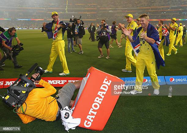 David Warner of Australia laughs as a camera man fall over during the victory lap for the 2015 ICC Cricket World Cup final match between Australia...