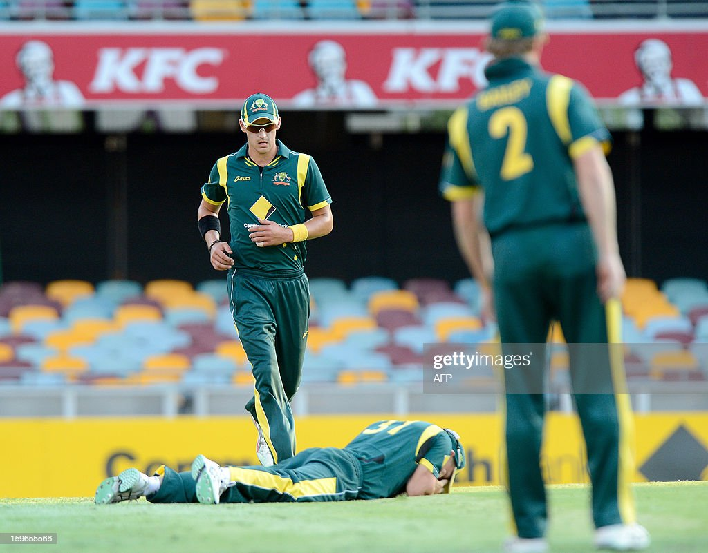 David Warner (C) of Australia lays on the gound in frustration after dropping a catch against Sri Lanka during their one-day international cricket match at the Gabba in Brisbane on January 18, 2013. AFP PHOTO / Bradley KANARIS USE
