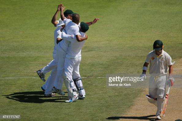 David Warner of Australia leave the field after getting out to Vernon Philander of South Africa as South African players celebrate during day three...