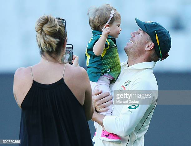David Warner of Australia plays with her daughter Ivy as wife Candice Warner takes photos during day four of the Second Test match between Australia...