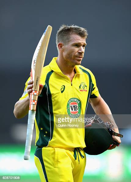 David Warner of Australia raises his bat to the crowd as he leaves the field after making a century during game three of the One Day International...