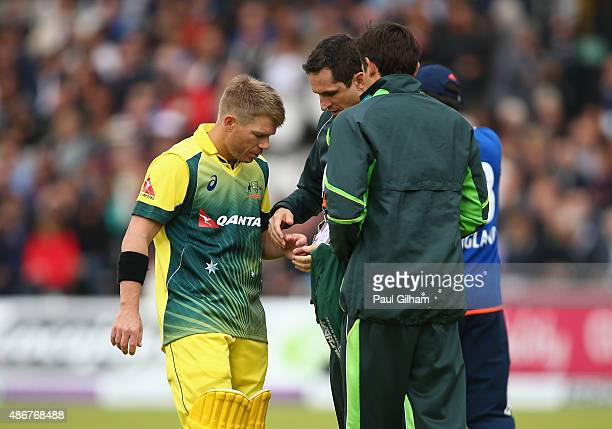 David Warner of Australia receives treatment on his hand after picking up an injury from the bowling of Steven Finn of England during the 2nd Royal...