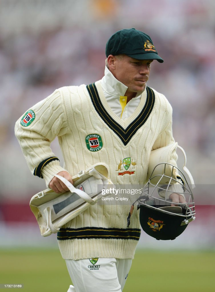 David Warner of Australia runs a helmet and shin guard off the pitch during day one of the 1st Investec Ashes Test match between England and...