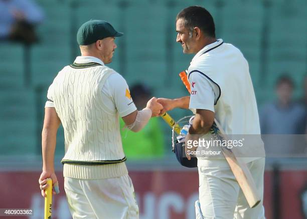 David Warner of Australia shakes hands with MS Dhoni of India as the game was called off for a draw during day five of the Third Test match between...