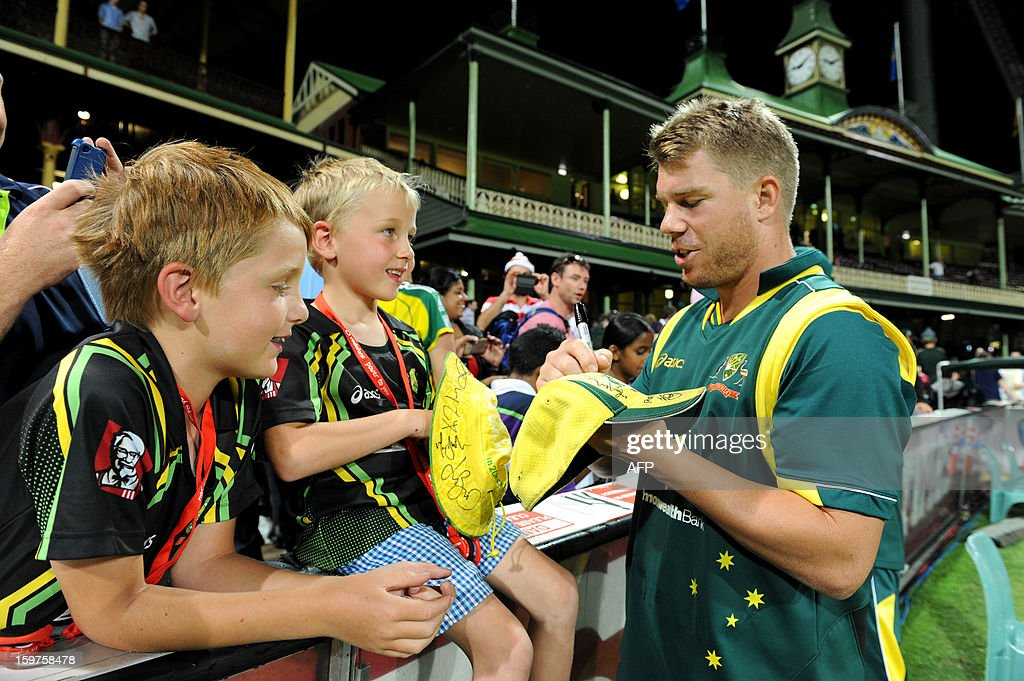 David Warner of Australia (R) signs autographs for nine-year-old Laythen Carlise (L) and his five-year-old brother Balin (C) after play was abandoned due to rain at the fourth one-day international between Australia and Sri Lanka at the Sydney Cricket Ground on January 20, 2013. AFP PHOTO / DAN HIMBRECHTS USE