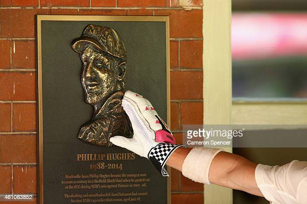 David Warner of Australia touches a bronze plaque tributing the late Australian cricketer Phillip Hughes mounted on the wall outside the Australian...