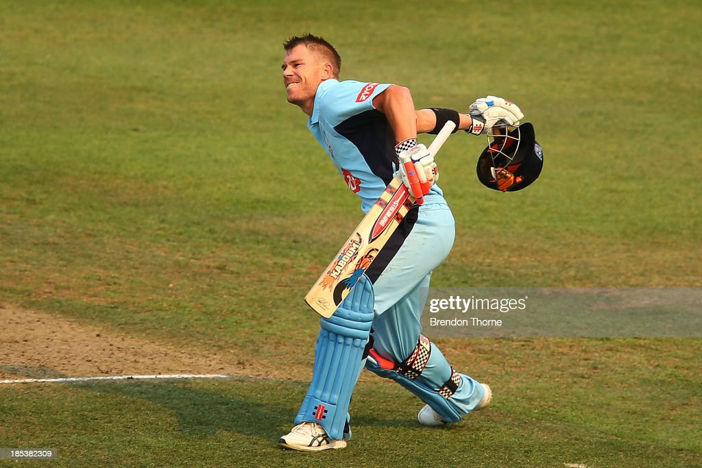 David Warner of the Blues celebrates scoring a century during the Ryobi Cup match between the New South Wales Blues and the Victorian Bushrangers at North Sydney Oval on October 20, 2013 in Sydney, Australia.
