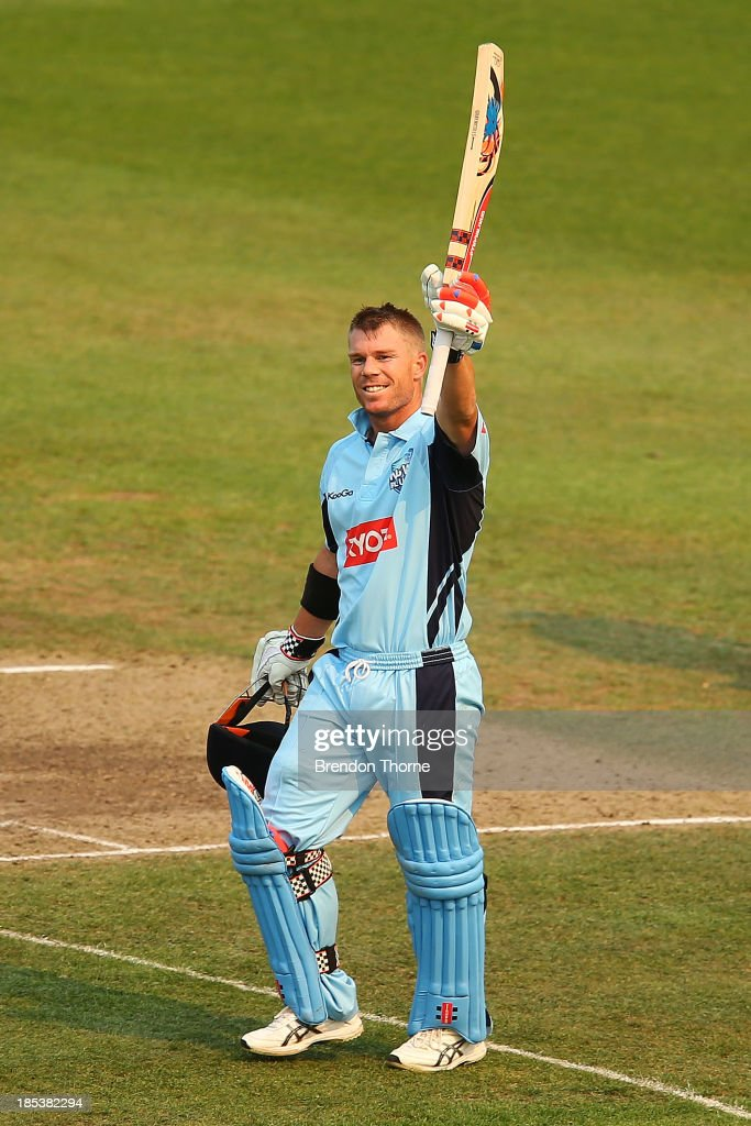 David Warner of the Blues raises his bat in celebration of scoring a century during the Ryobi Cup match between the New South Wales Blues and the Victorian Bushrangers at North Sydney Oval on October 20, 2013 in Sydney, Australia.