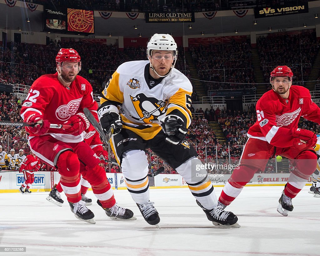 David Warsofsky #5 of the Pittsburgh Penguins races after the puck followed by Thomas Vanek #62 and Xavier Ouellet #61 of the Detroit Red Wings during an NHL game at Joe Louis Arena on January 14, 2017 in Detroit, Michigan.