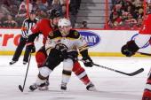 David Warsofsky the Boston Bruins skates against Matt Kassian of the Ottawa Senators during an NHL game at Canadian Tire Centre on December 28 2013...