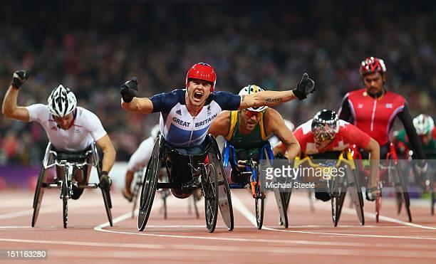 David Weir of Great Britain celebrates as he wins gold ahead of silver medallist Kurt Fearnley of Australia and bronze medallist Julien Casoli of...