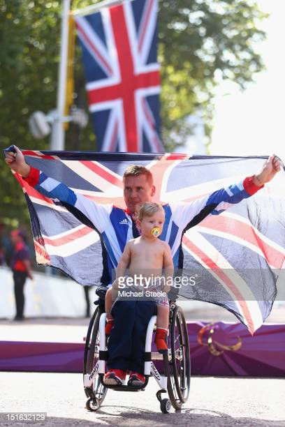 David Weir of Great Britain poses with his fourth gold medal of the Paralympic Games with his son Mason Weir after victory in the Men's T54 Marathon...