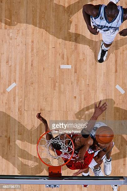 David Wesley of the Charlotte Hornets puts a shot up over Lorenzen Wright of the Atlanta Hawks during the game on April 12 2000 at Charlotte Colesium...
