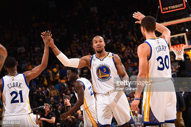 David West Ian Clark and Stephen Curry of the Golden State Warriors celebrate during a game against the Miami Heat on January 10 2017 at ORACLE Arena...
