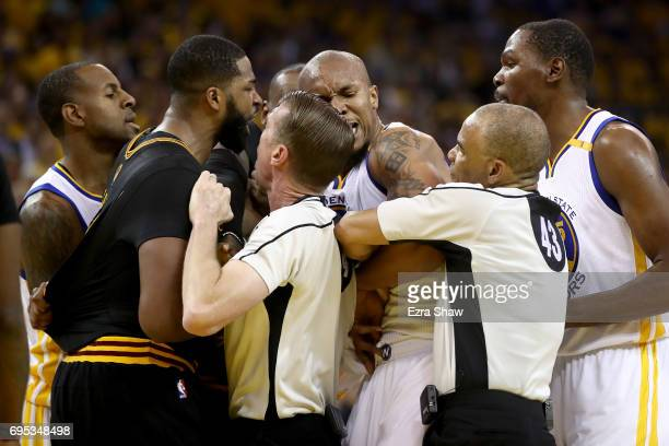 David West of the Golden State Warriors and Tristan Thompson of the Cleveland Cavaliers are separated by referee Ed Malloy and referee Dan Crawford...
