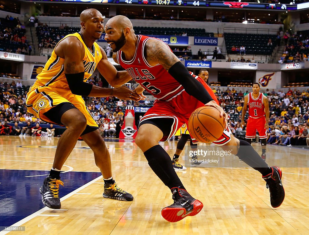 David West #21 of the Indiana Pacers defends as <a gi-track='captionPersonalityLinkClicked' href=/galleries/search?phrase=Carlos+Boozer&family=editorial&specificpeople=201638 ng-click='$event.stopPropagation()'>Carlos Boozer</a> #5 of the Chicago Bulls dribbles the ball on the baseline on October 5, 2013 at Bankers Life Fieldhouse in Indianapolis, Indiana. Chicago defeated Indiana 82-76.