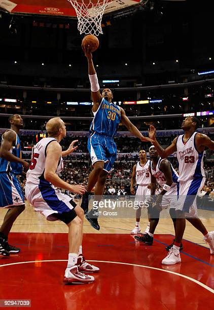 David West of the New Orleans Hornets drives to the basket past Chris Kaman and Marcus Camby of the Los Angeles Clippers in the second half at...